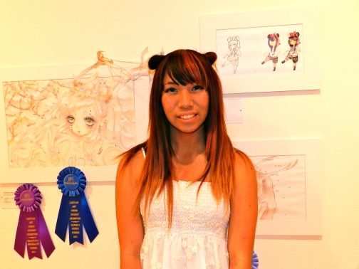 This soon to be high school junior poses in front of her work, which received top honors in the student contest.